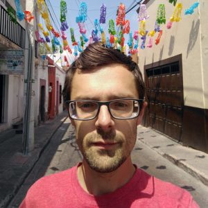 Jordan Schulz on a Mexican street with colored paper decorations hanging behind him